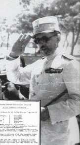 Ο Γεώργιος Τσολάκογλου με τη λευκή επίσημη θερινή στολή του, το 1941. Το σημαντικό στη φωτογραφία αυτή είναι στο πηλίκιο. Διακρίνεται το ιδιότυπο εθνόσημο που είχε η Ελληνική Πολιτεία όπως λεγόταν το κατοχικό κράτος.