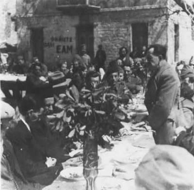 Μάιος 1944, Εδρα ΠΕΕΑ, Κεράσοβο Ευρυτανίας: Υπαίθριο τραπέζι, πιθανόν εορτασμός Πάσχα. Ο Στέφανος Σαράφης όρθιος ομιλητής και σύνθημα 'Ψηφίστε όλοι ΕΑΜ'