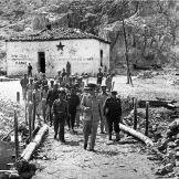 1948-xx-xx - Η ειρωνεία της Ιστορίας. Ο βασιλιάς Παύλος επισκέπτεται μια ανταρτόπληκτη περιοχή,ενώ το σύνθημα στον τοίχο του ερειπίου είναι «Ζήτω ο αρχηγός Μάρκος»