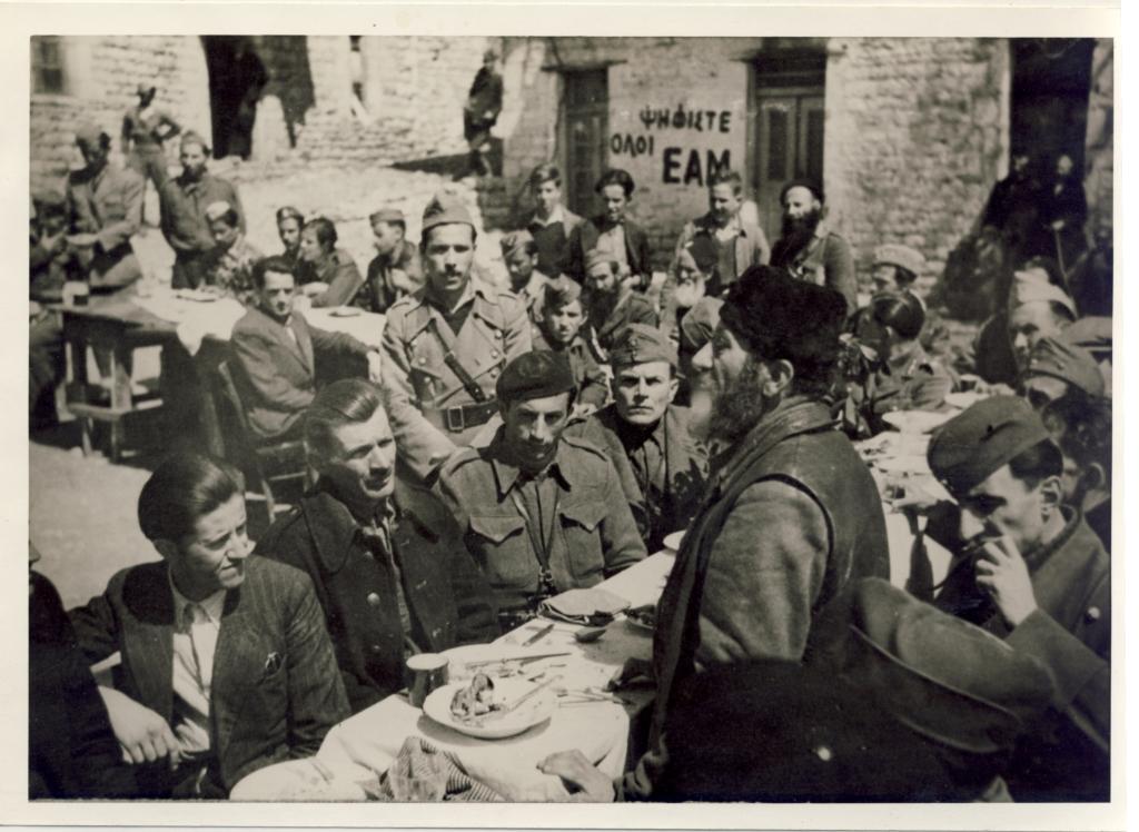 Μάιος 1944, Εδρα ΠΕΕΑ, Υπαίθριο τραπέζι: Παπασταματιάδης, Μακρίδης (ή Παπαθεοδωρόπουλος, Εθνοσύμβουλος Πελοποννήσου), Λευτέρης Αποστόλου. Στον τοίχο σύνθημα 'Ψηφίστε όλοι ΕΑΜ'.