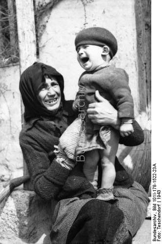 Μια άλλη γιαγιά προσπαθεί να καθησυχάσει το μωράκι, προφανώς εγγονάκι της, μετά από την καταστροφή του χωριού από τον ναζί κατακτητή. Φωτογραφία από τα γερμανικά αρχεία