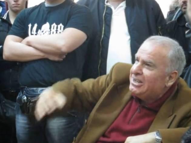 """Φωτογραφία από ομιλία του Μιχαλολιάκου. Οι γενιές του ελληνικού εθνικοσοσιαλισμού συναντιούνται. Επάνω από τον καθισμένο Γιώργο Χαρλαύτη (παλιό στέλεχος της 4ης Αυγούστου και του ΕΣΕΣΙ, τη νύχτα του Πολυτεχνείου ήταν στα γραφεία Μπουμπουλίνας, συγκατηγορούμενος του Καλέντζη και του Πλεύρη για βόμβες κ.λπ) ο νεαρός χρυσαβγίτης με το """"14/88"""" στην μπλούζα του."""