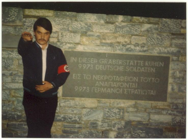 """Ο Χρήστος Παππάς στο γερμανικό νεκροταφείο Διονύσου-Ραπεντόζας. Φυσικά, δεν είναι Ελληνας χιτλερόψυχος νεοναζί με περιβραχιόνιο-σβάστικα σε χιτλερικό-ναζιστικό χαιρετισμό """"Χάιλ Χίτλερ"""". Είναι Ελληνας """"πατριώτης εθνικιστής"""", με γαμμάδιο-περιβραχιόνιο σε αρχαιοελληνικό χαιρετισμό, ενώ αποδίδει φόρο τιμής σε Ελληνες μαχητές του ελληνικού πολιτισμού."""