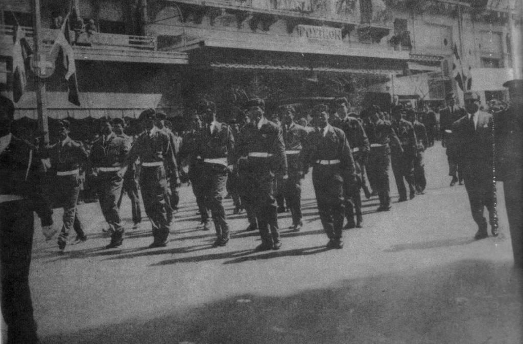 """Οδός Πανεπιστημίου, 23 Μαρτίου 1963. Το τμήμα Νέων των Ελπιδοφόρων παρελαύνει με πλήρεις στολές, διάσημα, αμφιμασχάλια και εξαρτύσεις, κατόπιν εγκυκλίου του Υπουργείου Παιδείας και του υπουργού Γεωργίου Ράλλη. Ο ομαδάρχης τους με πολιτικά δίπλα στον αστυφύλακα. Στην ίδια παρέλαση μπροστά στον Αγνωστο Στρατιώτη, συμμετείχε και άλλο άγημα, των λεγομένων """"Μελανοχιτώνων"""", επίσης με επίσημη άδεια απ' το υπουργείο. Η φωτογραφία από το περιοδικό """"Δρόμοι της Ειρήνης"""". Την ίδια στιγμή, αντιπροσωπεία σπουδαστών που προσπάθησε να καταθέσει στεφάνι στο άγαλμα του Ρήγα Φεραίου στα Προπύλαια δέχτηκε επίθεση από αστυφύλακες. Ποδοπάτησαν το στεφάνι και ακολούθησαν τραμπουκισμοί και συλλήψεις."""