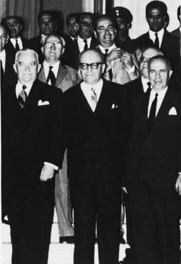 Η τρίτη κατά σειράν κυβέρνηση που στηρίχτηκε στους αποστάτες που αποσκίρτησαν από την Ενωση Κέντρου. Ο πρωθυπουργός Στέφανος Στεφανόπουλος, οι αποστάτες («Η απόσπασις των αναγκαίων βουλευτών έγινε με εξαγορά, με εξαγορά συνειδήσεων, με υπουργοποίηση ανθρώπων που ποτέ δεν θα εγίνοντο υπουργοί, υπό άλλας συνθήκας», σημείωνε αργότερα ο Παναγιώτης Κανελλόπουλος), και πίσω, κοντεύει να τρελαθεί απ' τη χαρά του, ο Μητσοτάκης.