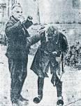 Ενας από τους άνδρες των ταγμάτων ασφαλείας του Ι. Ράλλη υποβάλλει σε σωματική έρευνα, για λογαριασμό των Γερμανών, Ελληνα πολίτη στην Αθήνα, αφού πρώτα τον διέταξε «ψηλά τα χέρια»