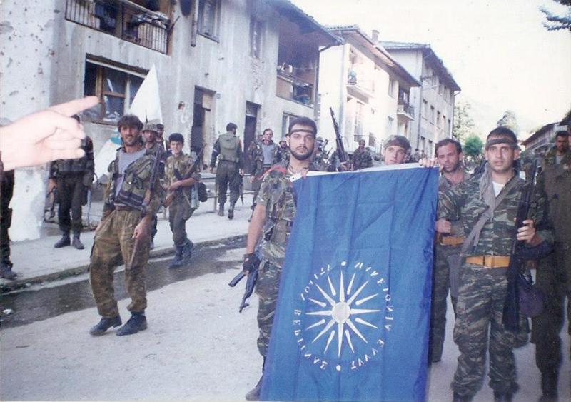 Σρεμπρένιτσα Βοσνίας, 11 Ιουλίου 1995, την ημέρα της πτώσης της πόλης και της αρχής της μεγαλύτερης ανθρωποσφαγής από τον Β' ΠΠ. Πρόκειται για σημείο προέλασης προς την πόλη των Σερβοβόσνιων, από όπου προηγουμένως έχει περάσει ο Μλάντιτς με το επιτελείο του και τους αρχηγούς των παραστρατιωτικών του. Διακρίνονται το τότε στέλεχος της Χρυσής Αυγής, Τζανόπουλος Σπύρος (λοχίας της ΕΕΦ), ο Ζαβιτσάνος Δημήτριος (αρχιλοχίας της ΕΕΦ) και μαζί τους -άλλοι φαίνονται κι άλλοι όχι- βρίσκονται οι Βασιλειάδης Τρύφων, Φλορίν Αννα (Ελληνορουμάνος), Σχιζάς Βασίλης, Κυριακίδης Κ., Λυμπερίδης Γ. και Δημουλάς Xαράλαμπος.