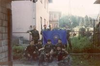 Βλασένιτσα, 1995, άνδρες της ΕΕΦ με την σημαία της Βεργίνας. Διακρίνεται το στέλεχος της Χρυσής Αυγής Τζανόπουλος Σπύρος (λοχίας της ΕΕΦ) και οι Ζαβιτσάνος Δημήτριος (αρχιλοχίας της ΕΕΦ), Kαλτσούνης Κωνσταντίνος, Αννα Φλορίν, Μήτκος Αντώνιος (διοικητής της ΕΕΦ), Βασιλειάδης Τρύφων (υποδιοικητής της ΕΕΦ), Σχιζάς Βασίλης, Κυριακίδης Κ., Λυμπερίδης Γ. και Δημουλάς Xαράλαμπος. Το σήμα με τα τρία δάχτυλα που κάνει στην κάμερα ο Ζαβιτσάνος είναι το σερβικό εθνικιστικό σήμα του νέου σερβικού μεγαλοϊδεατισμού που έκαναν όλοι οι Σέρβοι από τότε που ξεκίνησε η διάλυση της Γιουγκοσλαβίας και σε όλη τη διάρκεια του πολέμου. Και ακόμα το κάνουν.