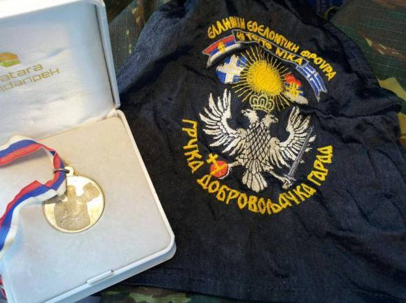 Αριστερά το Μετάλλιο του Λευκού Αγγέλου, ανώτατη διάκριση από τη Σερβοβοσνιακή Δημοκρατία προς τους Ελληνες εθελοντές της ΕΕΦ και δεξιά το φορετό σήμα της ΕΕΦ, με τον αποτυχημένο ήλιο της Βεργίνας