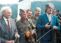 Περιοχή Βλασένιτσα (Vlasenica), κοντά στη Σρεμπρένιτσα, εκεί όπου βρίσκεται η αυτοκρατορία, αλλά και ο τόπος καταγωγής του Zβόνκο Μπάγιαγκιτς (Zvonko Bajagic), 30 Σεπτεμβρίου 1992. Στη φωτογραφία ο Ράντοβαν Κάρατζιτς σε ομιλία κατά την διάρκεια της μεγάλης συγκέντρωσης-συλλαλητηρίου-κηδείας Σέρβων θυμάτων των Μουσουλμάνων, με σκοπό να φανατιστούν οι Σερβοβόσνιοι. . Ο Μπάγιαγκιτς δίπλα στον ηγέτη των Σερβοβόσνιων, με το χαρακτηριστικό σερβικό εθνικό καπέλο Sajkaca.