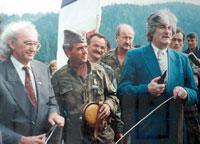 Περιοχή Βλασένιτσα (Vlasenica), κοντά στη Σρεμπρένιτσα, εκεί όπου βρίσκεται η αυτοκρατορία, αλλά και ο τόπος καταγωγής του Zβόνκο Μπάγιαγκιτς (Zvonko Bajagic), 30 Σεπτεμβρίου 1992. Στη φωτογραφία ο Ράντοβαν Κάρατζιτς σε ομιλία κατά την διάρκεια της μεγάλης συγκέντρωσης-συλλαλητηρίου-κηδείας Σέρβων θυμάτων των Μουσουλμάνων, με σκοπό να φανατιστούν οι Σερβοβόσνιοι. Ο Μπάγιαγκιτς δίπλα στον ηγέτη των Σερβοβόσνιων, με το χαρακτηριστικό σερβικό εθνικό καπέλο Sajkaca.