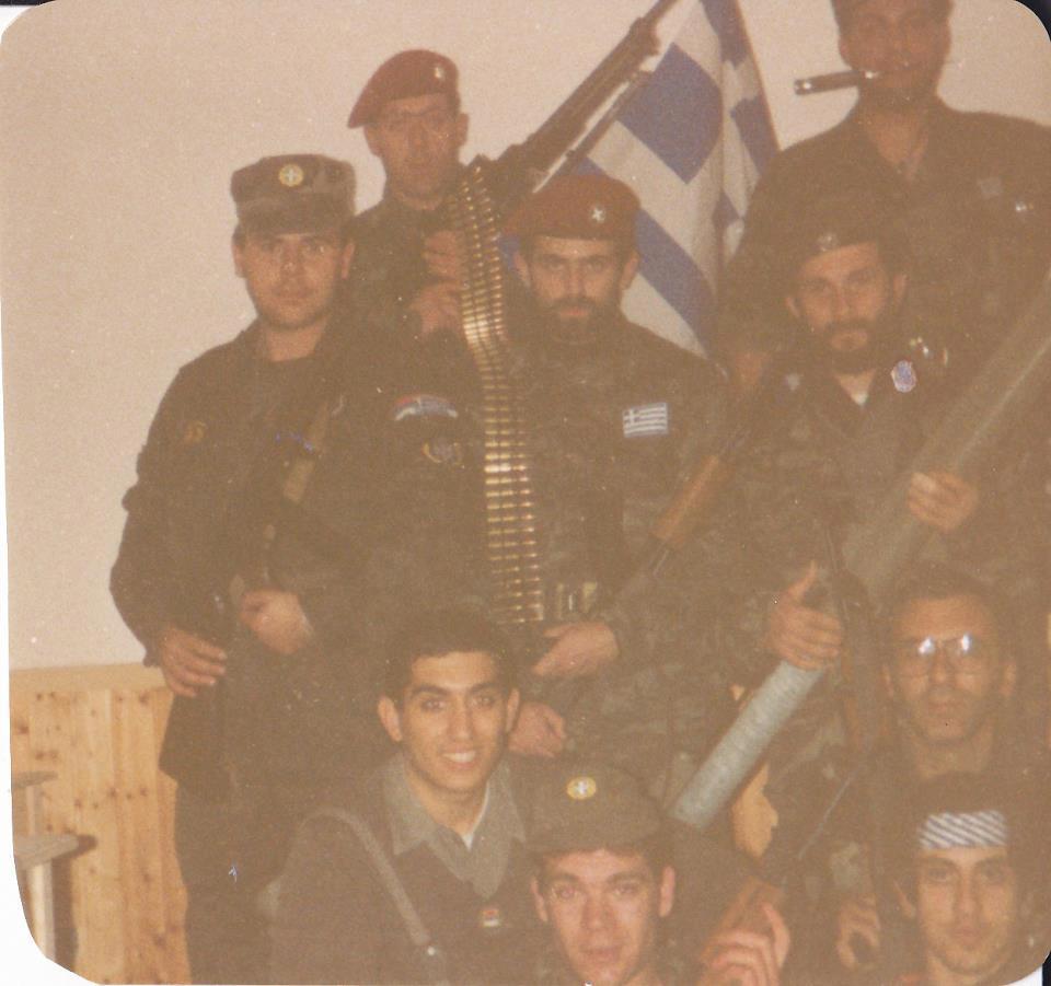Βλασένιτσα Βοσνίας, Φεβρουάριος 1995, προφανώς στη βάση του στρατοπέδου της ΕΕΦ ή ίσως σε κάποιο από τα κατασχεμένα μουσουλμανικά οικήματα που είχαν παραχωρηθεί στους Ελληνες, κατόπιν διαταγής του Μλάντιτς. Διακρίνονται οι Μήτκος Αντώνιος (διοικητής της ΕΕΦ), Βασιλειάδης Τρύφων (υποδιοικητής της ΕΕΦ), Μουρατίδης Γιώργος, Καθάριος Κυριάκος, Κώστας (αγνώστων λοιπόν στοιχείων, ίσως να πρόκειται για τον καταγεγραμμένο εθελοντή Κώστα Λαμπρόπουλο), Λάτσιος Αγγελος του 10ου Αποσπάσματος Σαμποτάζ, Νικολαΐδης Νίκος και το μέλος της Χρυσής Αυγής ΜΜ. Επιδεικνύουν -υποθέτουμε- τον βαρύ οπλισμό τους.