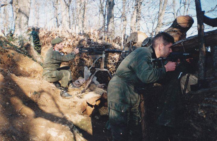Τέοτσακ, Βοσνία, Απρίλιος 1995. Η ώρα του παιδιού. Διακρίνονται οι Μήτκος Αντώνης και Βασιλειάδης Τρύφωνας σε χαράκωμα με οπλοπολυβόλο Μπράουνινγκ, υποτίθεται πυροβολούν τον εχθρό που είναι κοντά. Καταλαβαίνετε τώρα: Δέχονται επίθεση, και ο τρίτος της παρέας (αυτός που βγάζει τη φωτογραφία), αντί να πιάσει το όπλο, αφού υποτίθεται -λέμε τώρα- κινδυνεύει η ζωή του, αυτός πιάνει τη φωτογραφική μηχανή. Εντελώς παιδάκια που παίζουν πόλεμο, δηλαδή, που περνάνε όλους τους άλλους για χαζούς και θύματα που μπορούν να παραμυθιάσουν.
