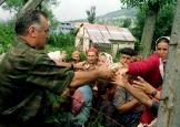 Η συγκεκριμένη σκηνή δεν έχει αποτυπωθεί σε βίντεο. Η φωτογραφία από το Reuters με λεζάντα: «Bosnian Serb Army commander General Ratko Mladic hands out cans of beverages to Bosnian Muslims, refugees from Srebrenica, as they wait to be transported from eastern Bosnian village of Potocari to Muslim held Kladanj near Olovo on July 12, 1995».