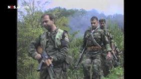 Ημέρες των θηριωδιών, 13 Ιουλίου 1995, Σρεμπρένιτσα, Βοσνία. Δεύτερος στη φάλαγγα, το μέλος της Χρυσής Αυγής Τζανόπουλος Σπύρος. Με τα όπλα γεμάτα και το δάχτυλο στην σκανδάλη, ξεκινάνε μαζί με Σέρβους ένοπλους παραστρατιωτικούς για κυνήγι Μουσουλμάνων, πιθανώς με την μέθοδο της ενέδρας.