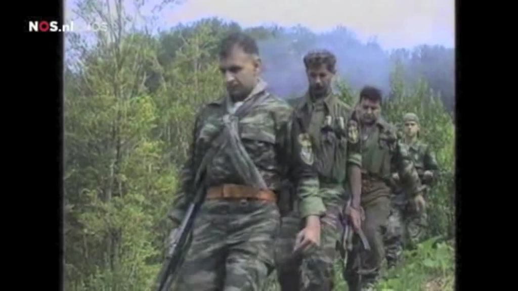 Ημέρες των θηριωδιών, 13 Ιουλίου 1995, Σρεμπρένιτσα, Βοσνία. Οι τέσσερις από τους συνολικά δέκα της ΕΕΦ που βρίσκονταν ακριβώς στους τόπους των μαζικών εκτελέσεων αόπλων και αιχμαλώτων. Με τα όπλα γεμάτα και το δάχτυλο στην σκανδάλη, ξεκινάνε μαζί με Σέρβους ένοπλους παραστρατιωτικούς για κυνήγι Μουσουλμάνων, πιθανώς με την μέθοδο της ενέδρας. Το μέλος της Χρυσής Αυγής Τζανόπουλος Σπύρος, ο Ελληνορουμάνος Φλορίν Αννα κά.