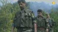 Ημέρες των θηριωδιών, 13 Ιουλίου 1995, Σρεμπρένιτσα, Βοσνία. Σε πρώτο πλάνο, ο Ελληνορουμάνος Φλορίν Αννα κά. Με τα όπλα γεμάτα και το δάχτυλο στην σκανδάλη, ξεκινάνε μαζί με Σέρβους ένοπλους παραστρατιωτικούς για κυνήγι Μουσουλμάνων, πιθανώς με την μέθοδο της ενέδρας.