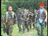 Στο κέντρο, το μέλος της Χρυσής Αυγής Τζανόπουλος Σπύρος. Πιο πίσω, στην εκκίνηση της φάλαγγας, οι υπόλοιποι, με τα όπλα γεμάτα και το δάχτυλο στην σκανδάλη, ξεκινάνε μαζί με Σέρβους ένοπλους παραστρατιωτικούς για κυνήγι Μουσουλμάνων, πιθανώς με την μέθοδο της ενέδρας. Ημέρες των θηριωδιών, 13 Ιουλίου 1995, Σρεμπρένιτσα, Βοσνία.