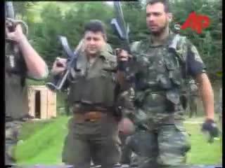 Σε πρώτο πλάνο, ο αρχιλοχίας Δημήτρης Ζαβιτσάνος καπνίζει ένα τελευταίο τσιγάρο πριν αρχίσει η 'δουλειά'. Με τα όπλα γεμάτα και το δάχτυλο στην σκανδάλη, ξεκινάνε μαζί με Σέρβους ένοπλους παραστρατιωτικούς για κυνήγι Μουσουλμάνων, πιθανώς με την μέθοδο της ενέδρας. Ημέρες των θηριωδιών, 13 Ιουλίου 1995, Σρεμπρένιτσα, Βοσνία.