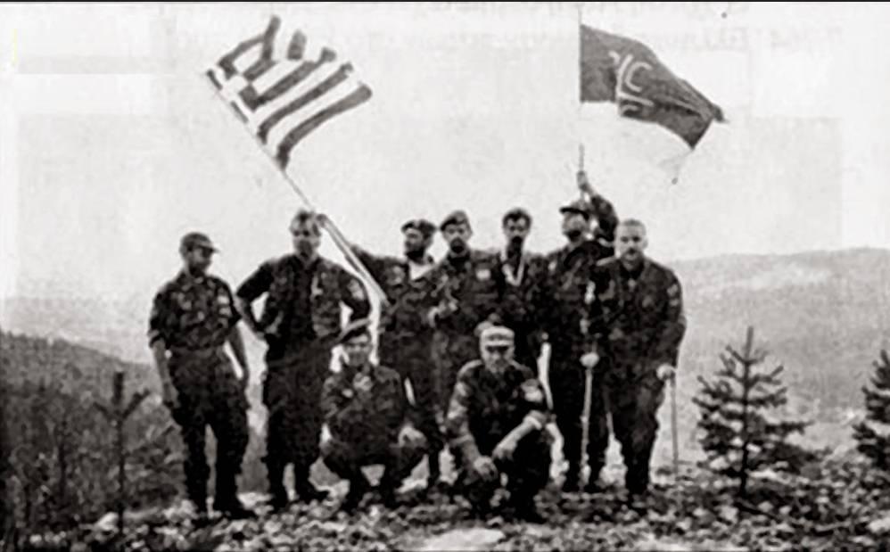 Βλασένιτσα, Βοσνία, 1995. Διακρίνονται με μια ελληνική και μια σερβική σημαία τα μέλη της Χρυσής Αυγής Μπέλμπας Απόστολος και Κουσουμβρής Σωκράτης με τις πατερίτσες και οι Κώστας, Βασιλειάδης Τρύφων, Δημητρίου Χρήστος, Φλορίν Αννα και άλλοι.