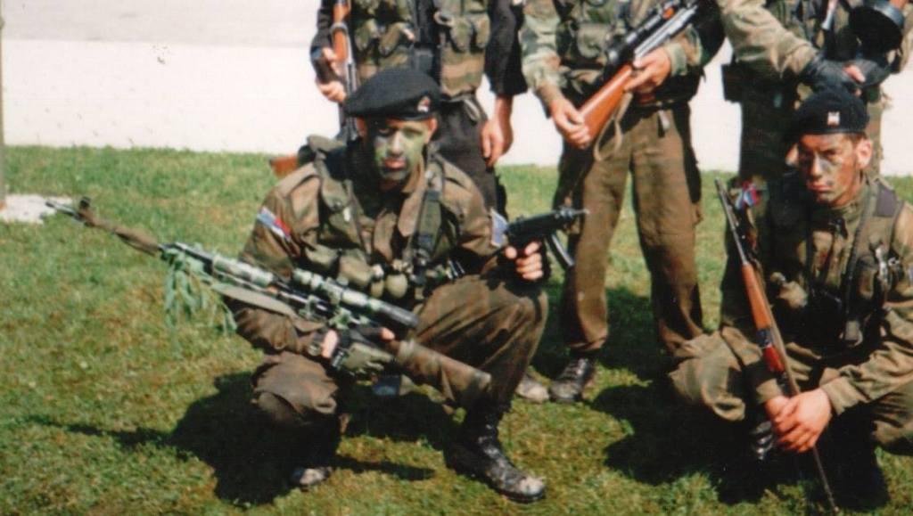 Με στολή παραλλαγής και τουφέκι σνάιπερ με διόπτρα στο ένα χέρι και κάποιο αυτόματο όπλο στο άλλο χέρι: Ελευθέριος Σπουργίτης, διωγμένο μέλος της ΕΕΦ.