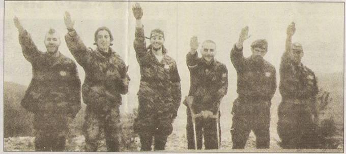 Ανοιξη του 1995: Η κλασική φωτογραφία στην περιοχή Βλασένιτσα, με τη χρυσαυγίτικη αφρόκρεμα της Ελληνικής Εθελοντικής Φρουράς ΕΕΦ. Εικονίζονται σε αρχαιοελληνικό (και καθόλου ναζιστικό) χαιρετισμό πρώην και νυν μέλη της Χρυσής Αυγής: Μπέλμπας Απόστολος, Μαυρογιαννάκης Μιχάλης, Σωκράτης Κουσουμβρής (με τις πατερίτσες), ο Κώστας και άλλοι δύο.
