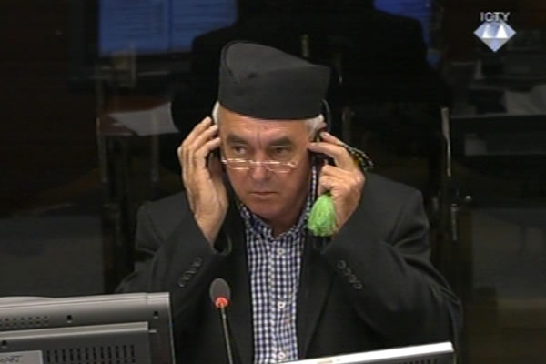Διεθνές Δικαστήριο Χάγης, 10/07/2010. Ο Zβόνκο Μπάγιαγκιτς καταθέτει υπέρ του Κάρατζιτς φορώντας το ίδιο καπέλο Sajkaca όπως στη Βλασένιτσα το 1992 και όπως στη Σρεμπρένιτσα το 1995, και κρατώντας ένα ορθόδοξο προσευχητάρι-κομποσκοίνι.