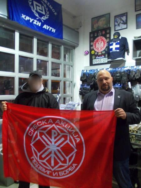 Ο Παναγιώταρος κι ένας Σέρβος νεοναζί Serbian Action υπό το βλέμμα του Αρκάν. Καλοκαίρι 2015, στο κατάστημα της Χρυσής Αυγής.