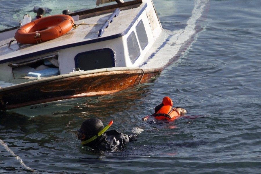 A Greek coast guard diver pulls the body of a refugee child away from a sunken wooden boat near the Greek island of Lesbos October 15, 2015. A baby, two children and a woman drowned on Thursday after their wooden boat and a coast guard vessel crashed during a migrant rescue operation off the island of Lesbos, the Greek coast guard said. The boat, which the coast guard said was old, sank after the crash and 31 persons were rescued. The coast guard did not provide further details on the incident or the nationality of the victims. (Photo by Giorgos Moutafis/Reuters)
