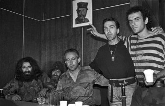 Αλλος ένας άγνωστος Ελληνας εθελοντής. Δεξιά με το ριγέ μπλουζάκι. Η φωτογραφία προέρχεται από Ιταλό δημοσιογράφο και είναι από το 1993, στην περιοχή Grbavica, στο Σαράγεβο. Προφανώς πρόκειται για κάποιον από τους πρώτους εθελοντές, που είχαν καταφτάσει στη Β-Ε σχετικά νωρίς, και πριν τη δημιουργία της ΕΕΦ. Σύμφωνα με δημοσιεύματα, τέσσερις από αυτούς είχαν καθήκοντα ελεύθερου σκοπευτή. Πράγματι, ο συγκεκριμένος εθελοντής εξιστόρησε στον Ιταλό δημοσιογράφο ότι έκανε ασκήσεις σκοποβολής στο Εβραϊκό Νεκροταφείο του Σαράγεβο, στοχεύοντας τα αστέρια του Δαβίδ στους τάφους. Του εξηγούσε, επίσης, ότι τα bar-code επάνω στα προϊόντα ήταν μέρος της εβραιομασονικής συνωμοσίας για να κατακτήσουν οι εβραιοσιωνιστές τον κόσμο, και γι' αυτό πήρε την απόφαση να πάει στη Βοσνία να πολεμήσει. Ακριβώς δίπλα του, με τον σταυρό, εγγονός τσέτνικ βοϊβόδα, γεννημένος στη Νέα Υόρκη, από οικογένεια διαφυγόντων μεγαλοτσέτνικ. Γύρισε στη Γιουγκοσλαβία, για να βρει τους άλλους τσέτνικ που βλέπουμε, για να πολεμήσουν μαζί «στο όνομα του Θεού και του έθνους», όπως είναι το διαχρονικό τους σύνθημα. Με τον αξιωματικό του JNA και το πορτρέτο του Μιχαήλοβιτς στον τοίχο και τα τρία δάχτυλα του Ελληνα αντισημίτη συνωμοσιολόγου, η σύνθεση δεν θα μπορούσε να είναι πιο χαρακτηριστική.