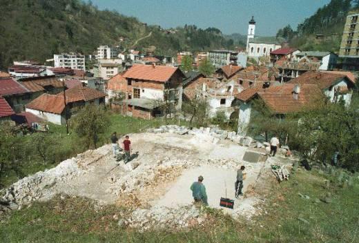 Μάιος 1997. Η λήψη από το Νότο κοιτάζοντας προς το Βορρά. Το 'Λευκό Τζαμί' (Bijela dzamija) της Σρεμπρένιτσα, γνωστό και ως το 'Τζαμί του Χατζή-Σκεντέρ Μπέη' ('Hadzi Skender-begova dzamija') ισοπεδωμένο. Στο βάθος η ορθόδοξη εκκλησία, η οποία δεν έχει πάθει καμία ζημιά. Σε αυτό το σημείο υψώθηκαν από την ΕΕΦ οι γνωστές τέσσερις σημαίες, ελληνική, σερβική, του Βυζαντίου και της Βεργίνας.
