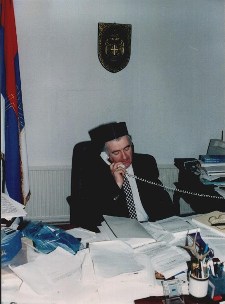 Ο Ράντοβαν Κάρατζιτς (Radovan Karadzic) στο γραφείο του με το χαρακτηριστικό σερβικό εθνικό καπέλο Sajkaca. Και στο γραφείο, προσεύχεται (την ώρα που σχεδιάζει εθνοκαθάρσεις).