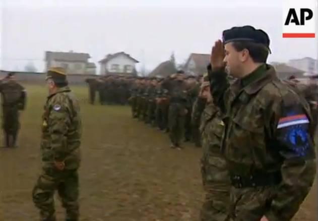 Ο λύκος που ουρλιάζει σε πρώτο πλάνο, στο περιβραχιόνιο του Milan Jolovic (Legenda). Μαζί με τον Μλάντιτς επιθεωρούν το στρατόπεδο της Βλασένιτσα τον Δεκέμβριο του 1995.