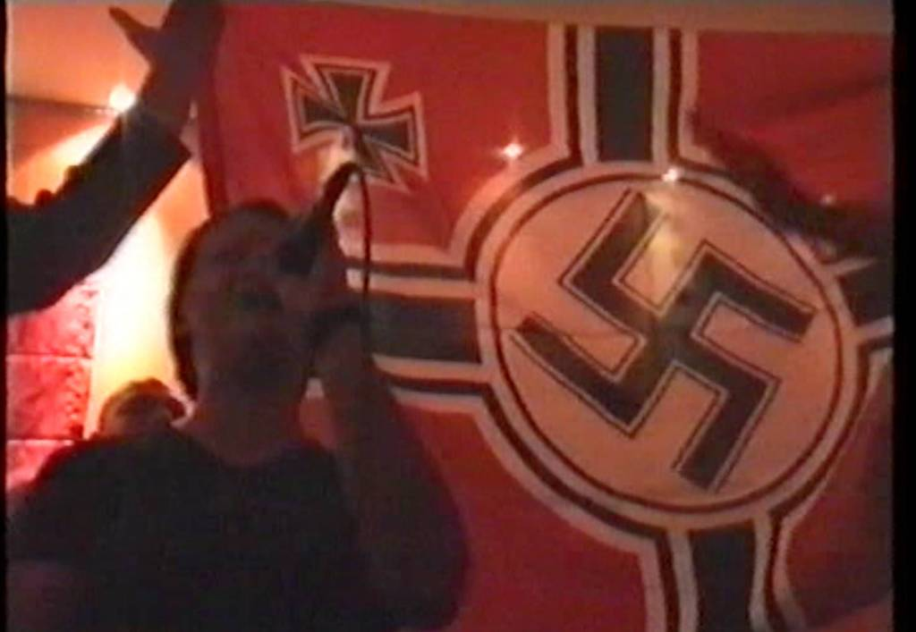 Η Annette τραγουδάει 'Deutschland, Deutschland uber alles' μπροστά από Σημαία της Βέρμαχτ