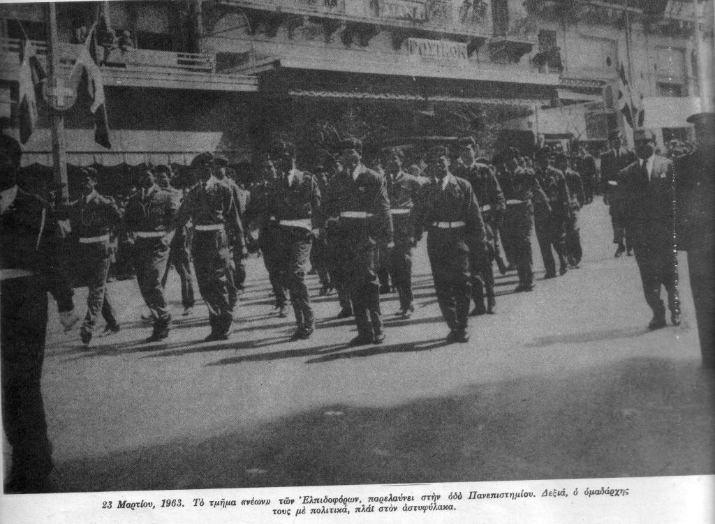 Οδός Πανεπιστημίου, 23 Μαρτίου 1963. Το τμήμα Νέων των Ελπιδοφόρων παρελαύνει με πλήρεις στολές, διάσημα, αμφιμασχάλια και εξαρτύσεις, κατόπιν εγκυκλίου του Υπουργείου Παιδείας και του υπουργού Γεωργίου Ράλλη. Ο ομαδάρχης τους με πολιτικά δίπλα στον αστυφύλακα. Στην ίδια παρέλαση μπροστά στον Αγνωστο Στρατιώτη, συμμετείχε και άλλο άγημα, των λεγομένων 'Μελανοχιτώνων', επίσης με επίσημη άδεια απ' το υπουργείο. Η φωτογραφία από το περιοδικό 'Δρόμοι της Ειρήνης'. Την ίδια στιγμή, αντιπροσωπεία σπουδαστών που προσπάθησε να καταθέσει στεφάνι στο άγαλμα του Ρήγα Φεραίου στα Προπύλαια δέχτηκε επίθεση από αστυφύλακες. Ποδοπάτησαν το στεφάνι και ακολούθησαν τραμπουκισμοί και συλλήψεις.