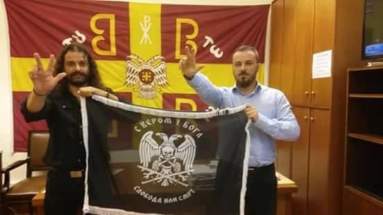 Στη φωτογραφία, οι βουλευτές της συμμορίας Κώστας Μπαρμπαρούσης και Ευάγγελος Καρακώστας, κατά πάσα πιθανότητα στα γραφεία της ΧΑ στη Βουλή, σηκώνουν για την κάμερα σημαία τσέτνικ (παράνομη στην πρώην Γιουγκοσλαβία επί Τίτο), παίρνοντας πόζα μπροστά από την μόνιμα αναρτημένη σερβική 'σημαία με τα 4C', τη 'βυζαντινή', τη λεγόμενη 'της εκκλησίας', ή αλλιώς σημαία των εθνοκαθάρσεων 1991-1999 («Είμαστε Σέρβοι, είμαστε Ορθόδοξοι, και θα σας εξοντώσουμε στο όνομα της πίστης και του έθνους μας»)'.
